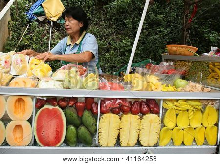 CHIANGMAI - NOVEMBER 30: Fresh fruits vendor wait for tourists at the Doi Suthep Temple in Chiang Mai on November 30, 2012. The food and tourism industry is a major income earner for Thailand.