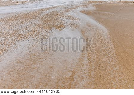 Waterscape Background. Sandy Beach With Milky Foam Waves. Nature And Environment Concept. Daylight.