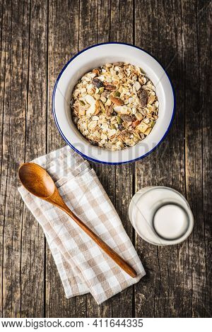Beakfast cereals in bowl. Healthy muesli with oat flakes, nuts and raisins on wooden table. Top view.