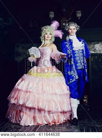 Indoors shot of a beautiful young woman in the Marie Antoinette style with her partner in the palace
