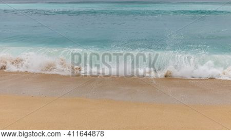 Seascape Background. Sandy Beach, Milky Foam Waves, Blue Ocean. Scenic Waterscape. Nature And Enviro