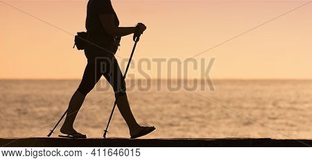 Woman Walking Along The Shore With Hiking Poles. Active Lifestyle Concept In Old Age