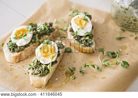 Sandwiches With Egg, Green Pesto, Micro Greens And Olive Oil On Paper On The Table. Closeup On Yello