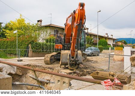 A Sewer Well Trench And A Crawler Excavator With A Rotating House Platform And Continuous Track On A