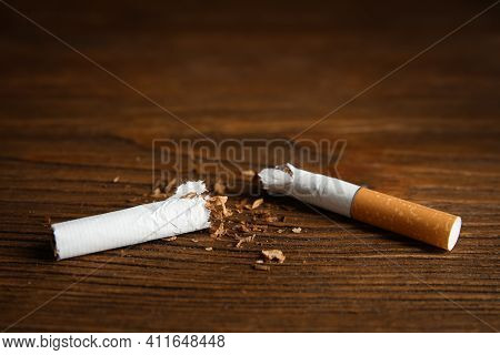 Broken Cigarette On Wooden Table, Closeup. Quitting Smoking Concept