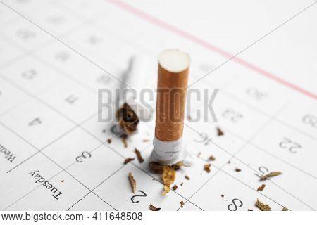 Broken Cigarette On Calendar Sheet, Closeup. Quitting Smoking Concept