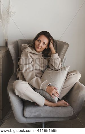 Woman Dressed In Comfy Loungewear Of Grey Color Sitting In A Cozy And Comfortable Armchair. Casual O