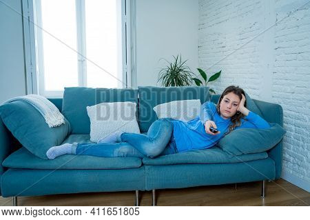 Bored Woman Watching Tv At Home Changing Channels With Remote Control
