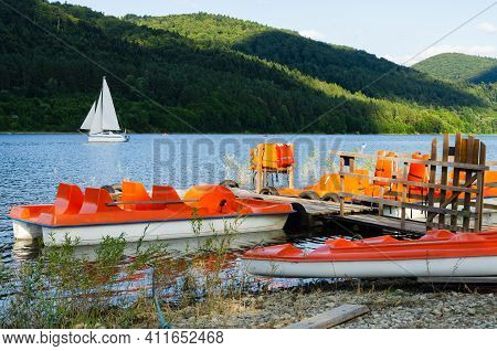 Orange Catamarans On Lake Moored At The Pier. Hipster Lifestyle. Tourism In National Park Holiday. A