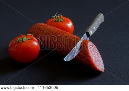 Tomatoes, Salami And A Sharp Knife On A Dark Background. Concept And Metaphor For Male Circumcision