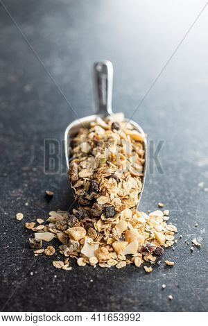 Beakfast cereals in scoop. Healthy muesli with oat flakes, nuts and raisins on black table.