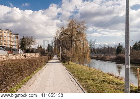 Early Spring In The Palace Park In The City Of Zagan In Western Poland. Alley With Benches And Elect