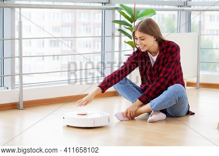 Woman Enjoys The Work Of A Smart Robot Vacuum Cleaner