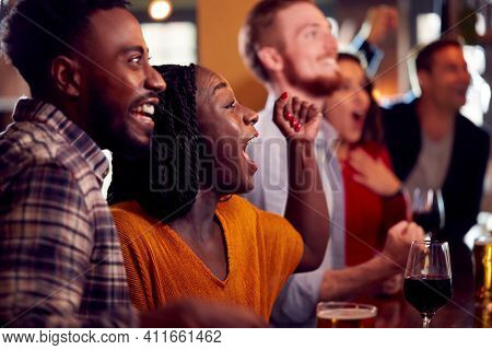 Group Of Excited Customers In Sports Bar Watching Sporting Event On Television