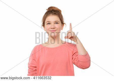 Your Promo Here. Young Girl 12-14 Years Old Pointing Index Finger Up For Advert Or Promotion, Recomm