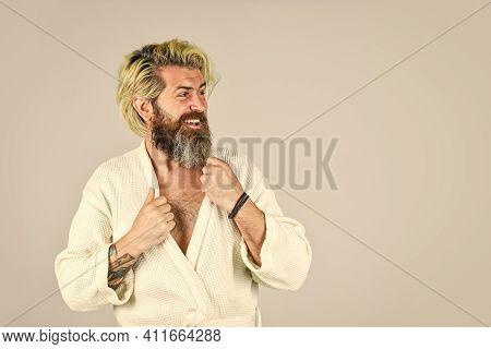 Man In Bathrobe In Bathroom. Hygiene And Spa. Spa Resort. Hotel Apartments. Bearded Guy Wearing Whit