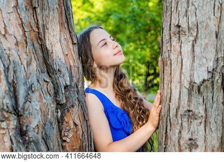 Little Kid Dreamer With Long Wavy Hair And Beauty Look Dream At Tree Trunk In Summer Park, Future