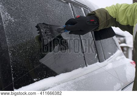 Winter Scene, Human Hand In Glove Scraping Ice From Of Car