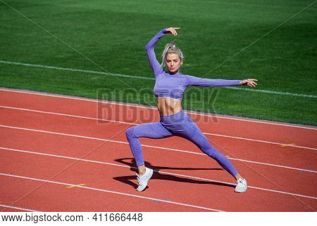 Athlete Warming Up. Warm Up On Outdoor Arena. Training And Workout. Athletic Female Coach. Woman Spo