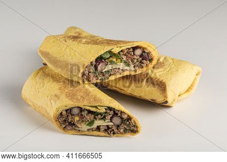 Tortilla Roll With Beef Beans And Fresh Herbs On A White Background, Isolated. Close-up With A Copy