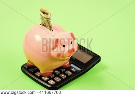 Economics And Finance. Piggy Bank Pink Pig Stuffed Dollar Banknote And Calculator. Financial Wellbei