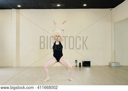 Fit Attractive Blond Woman In Black Leotard Dancing In Studio Alone And Looking At Camera