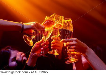 Group Of People Toast Drinks At Party In Dancing Club At Night . Social Gathering Event And Nightlif