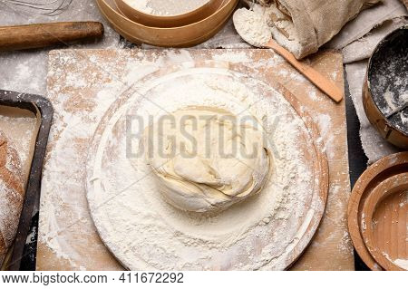 Kneaded Dough Of White Wheat Flour Lies On A Round Wooden Board, A Metal Bucket And A Wooden Rolling