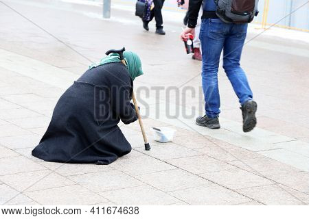 Beggar Old Woman Asks For Alms Sitting On A City Street. Poverty, Homeless And Begging Concept