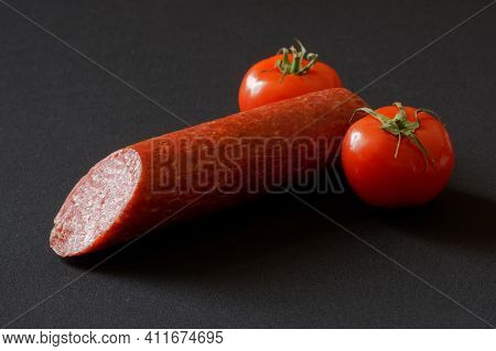 Red Tomatoes And Sliced Salami On A Dark Background. Anthropomorphism. Metaphor And Concept Of Ferti