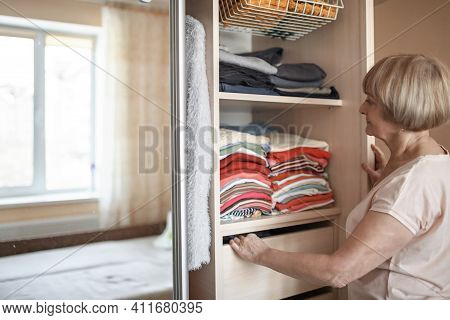 Senior Woman Choosing Outfit From Wardrobe Closet With Clothes And Home Stuff. Cleaning, Organizing