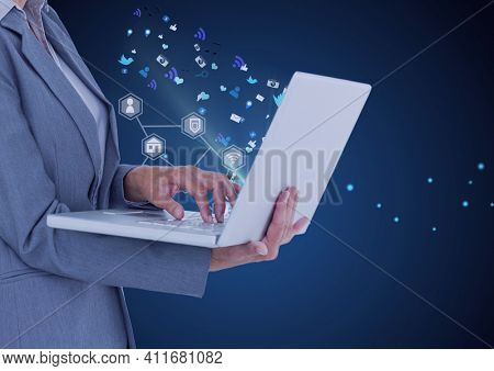 Network of digital icons over mid section of businesswoman using laptop against blue background. global networking and business technology concept
