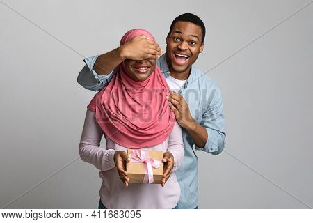 Young Black Man Making Surprise For His Girlfriend, Covering Her Eyes, Woman In Hijab Holding Festiv