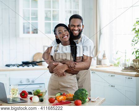 Portrait Of Romantic Black Spouses Embracing In Kitchen While Cooking Healthy Lunch Together, Cheerf