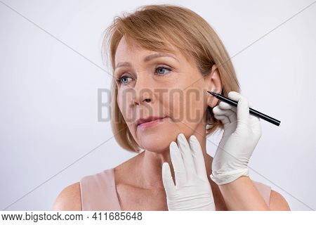 Doctor Drawing Marks On Senior Womans Face For Cosmetic Surgery Operation On Light Studio Background