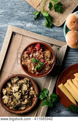 high angle view of a bowl with some spanish escalivada, made with different roasted vegetables, on a table next to some bread buns, a plate with some baby sweetcorn and a plate with cooked mushrooms