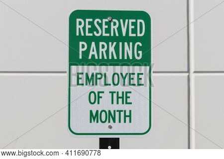 Reserved Parking For The Employee Of The Month Sign In White And Green Text.