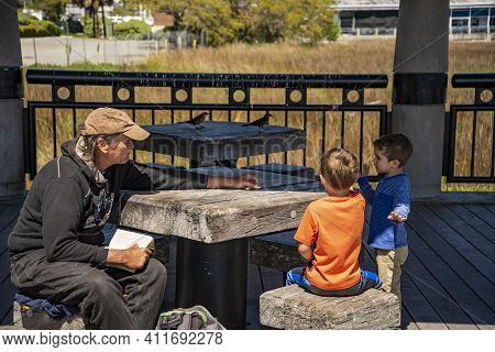 Charleston Sc - March 28, 2019: An Old Man And Two Little Children Playing On A Deck In Charleston,