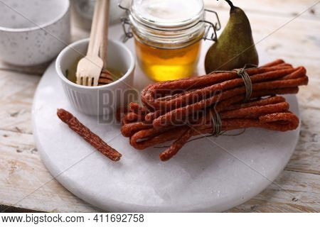 A Composition With Homemade, Smoked Kabanosy Sausage, Tied With String, On White Stony Cutting Board