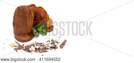 Two Custard Custard Eclairs Decorated With Chocolate Chips Powder And A Mint Leaf On A White Plate,