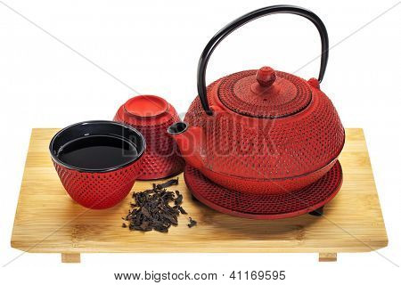 red hobnail tetsubin (traditional cast iron Japanese teapot) with a cup of oolong tea on a bamboo tray