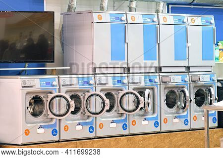 A Number Of Industrial Washing Machines In The Laundry Room. The Concept Of Self-service Dry Cleanin