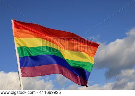 Waving Gay Pride Rainbow Flag In Blue Summer Sky, Copy Space. Realistic Flag Of Lgbt Organization In