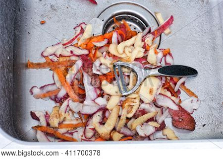 A Peeler Laying On A Pile Of Carrot, Radish And Potato Peels In A Sink. Close Up.