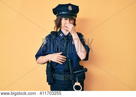 Young beautiful woman wearing police uniform smelling something stinky and disgusting, intolerable smell, holding breath with fingers on nose. bad smell