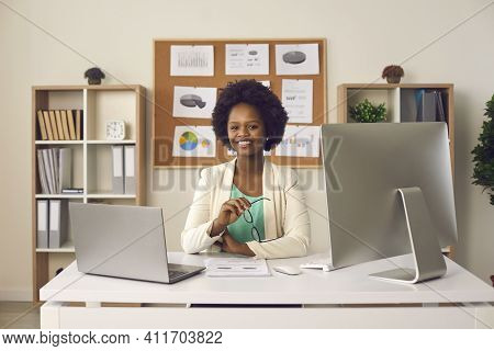 Happy Smiling Black Woman Sitting At Office Desk With Laptop And Desktop Computer