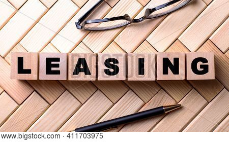 The Word Leasing Is Written On Wooden Cubes On A Wooden Background Next To A Pen And Glasses.