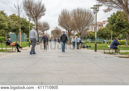 Palma De Mallorca, Spain; March 04 2021: People Wearing Face Masks Strolling Through The Parque De L
