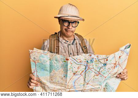 Middle age bald man wearing explorer hat holding map skeptic and nervous, frowning upset because of problem. negative person.