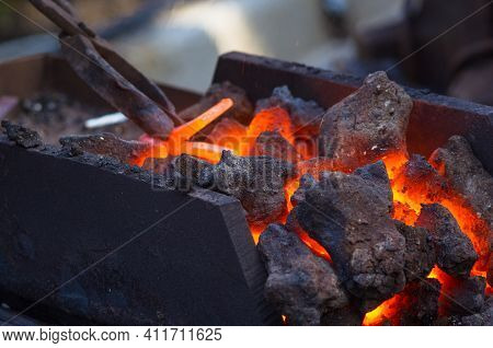 Blacksmith Furnace With Burning Coals, Tools, And Glowing Hot Metal Workpieces
